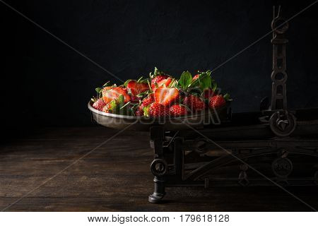 Fresh strawberries on vintage scales on dark background. Healty food concept with copy space.