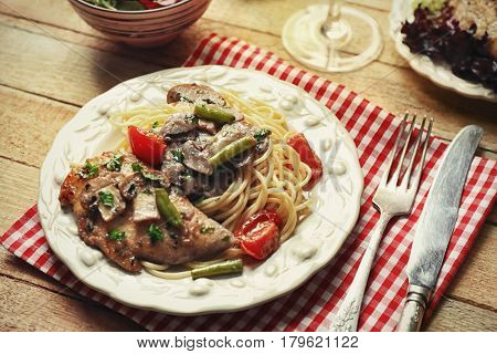Plate with delicious chicken marsala and spaghetti on table