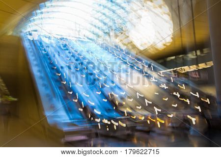 Modern architecture, Train station with escalators, supportive metal beams, tickets machine. Multiple exposure image.