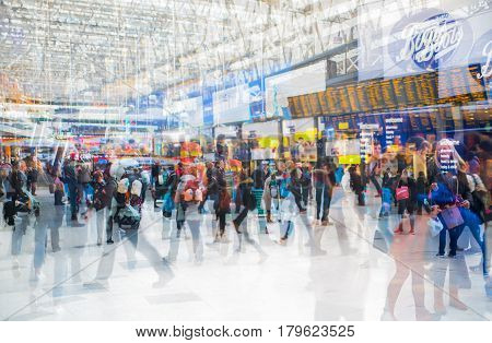 London, UK - November 30, 2016:  Multiple exposure image of lots of people walking and waiting for boarding in the Waterloo train station. Commuting rush hours concept, modern life.