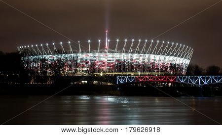 Night cityscape with National staduim (Stadion Narodowy) on the river Vistula in Warsaw, Poland