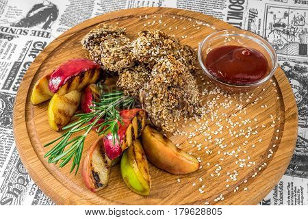 Fried meat with sesame apples and sauce on a wooden board