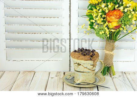 chocolate chip muffin baked in coffee cup with floral bouquet on whitewashed wood