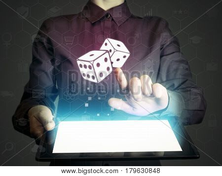 Image of a girl with tablet pc in her hands and dice icon. Concept of entertainment gambling fortune.
