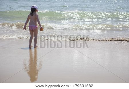 Little girl playing and splashing at beach shore. El Rompido Huelva Spain
