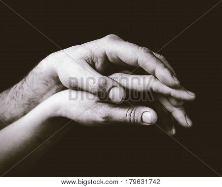 A gentle touch of two hands. Concept of LGBT love caring tolerance etc. Black and white toned image.