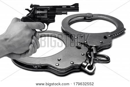 The gun in hand against the background of police handcuffs. Adventure and justice.