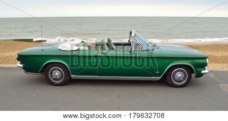 FELIXSTOWE, SUFFOLK, ENGLAND - AUGUST 27, 2016: Chevrolet Corvair convertible Classic American rear engine car parked on seafront promenade with the ocean in the background.