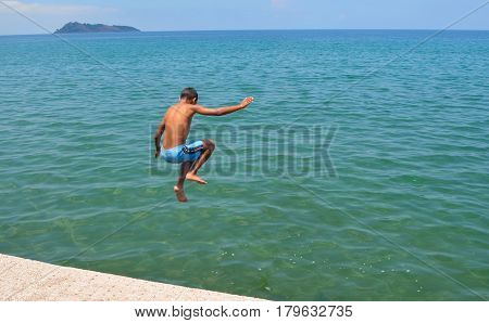 Boy jumping into sea off of a jetty on a  seafront on a sunny day.