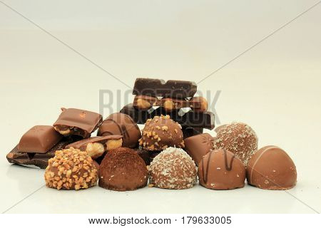 Different sorts of chocolates: bonbons and broken pieces of a chocolate bar