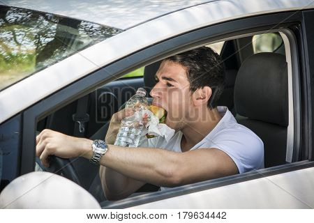 Young handsome man driving his car while eating food in the traffic