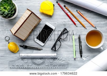 Construction office with architect working tools, mobile and cup of tea on light wooden table background top view