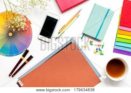 professional creative graphic designer desk with tools, mobile and cup on white background top view