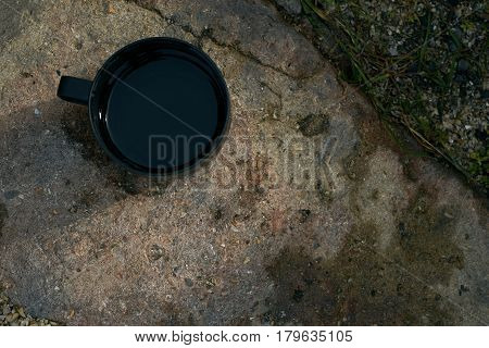 Top view of a large Enamel black mug with hot green tea on a painted stone. Tourist thermos cup with hot drink. Drinking tea outdoors.