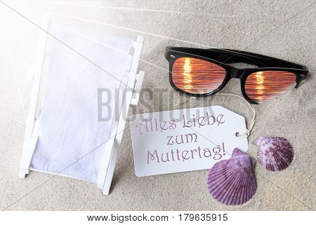 Sunny Summer Label With German Text Alles Liebe Zum Muttertag Means Happy Mothers Day. Flat Lay View. Summer Decoration With Deck Chair, Seashells And Sunglasses. Greeting Crad With Sand Background