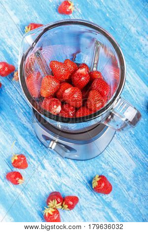 Fresh strawberries in blender on a wooden table. Next to the blender strewn strawberries. Vertical photo