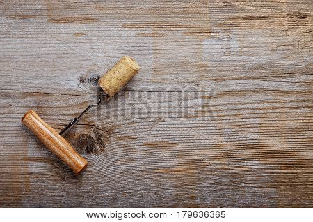 Corkscrew with a cork on a wooden table background with space for text horizontal photo