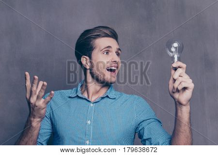A portrait of clever full of enthusiasm young man holding a light bulb