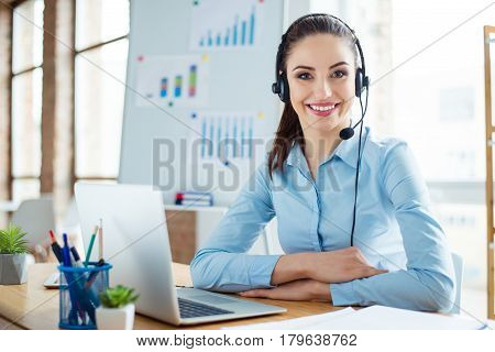 Portrait Of Cute Young Woman In Blue Shirt And Headphones Sitting At The Table And Working With Comp