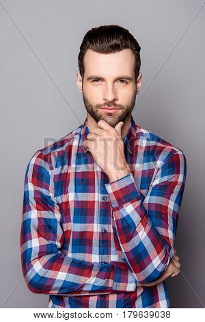 A Vertical Portrait Of Stylish Bearded Handsome Guy Touching His Chin And Posing Against Gray Backgr