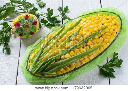 Delicious festive salad with eggs cheese prunes and canned corn. The original form of an ear of corn. Creative idea of a festive Easter dish
