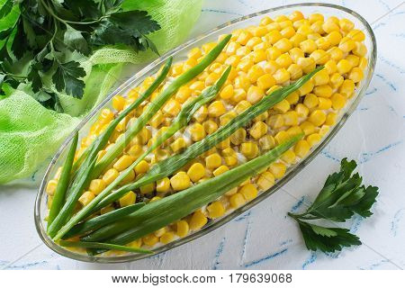 Delicious festive salad with eggs cheese prunes and canned corn. The original form of an ear of corn. Creative idea for holiday meals