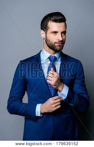 Portrait Of Serious Fashionable Handsome Man Posing In Blue Suit And Tie  Buttoning Cufflinks