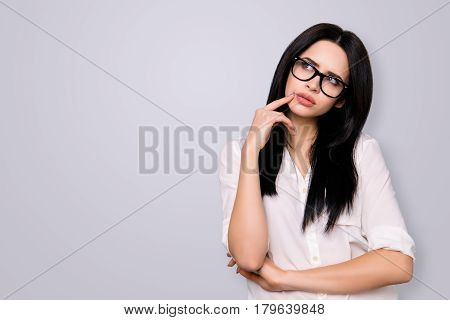Young Successful Woman In Spectacles Has New Idea And Think About It. She Looks To The Side On Copy