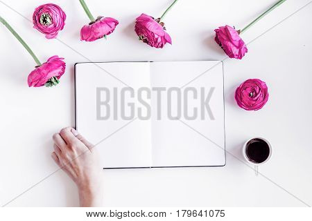 Modern spring design with bright pink flowers, copybook and hand on white desk background top view moke up
