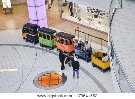 April 2 2017- People are seating inside mini train and standing outside of mini train waiting for the driver to operate to drive around inside of metropolis at metrotown located burnaby, BC Canada.