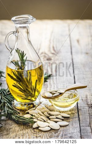 extra oil in carafe with pepitas and fresh rosemary on wooden desk background