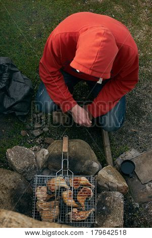 A young guy in a red sweatshirt and blue jeans at the weekend on nature cooking a shish kebab meat barbecue from chicken legs thighs on grill fire.