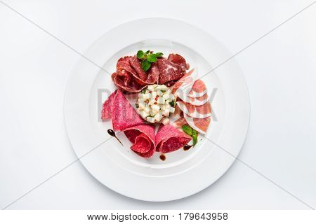 Dish of various types of meat-cutting on plate. Close-up, white background.