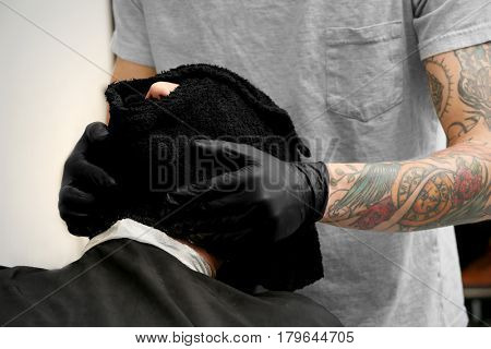 Hairdresser cleaning face of client with towel in barbershop