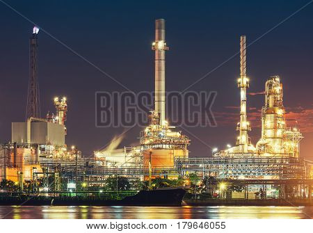 Oil refinery plant at twilight with sky background.