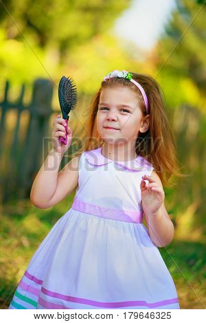 Beautiful girl with long hair combed tresses. A child holding a comb for the hair. Good kid walks in the courts against the background of the fence.