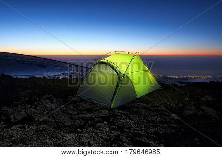 illuminated green tent at dawn in Etna Park, Sicily