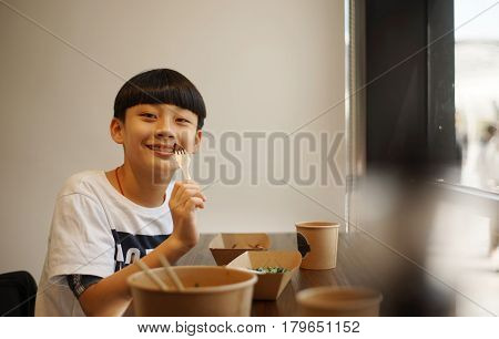 asian boy eating steak & smiling at camera