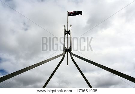 The Australian flag flying on top of Parliament House with cloudy sky. Flag flies on giant flagpole over Parliament House in Canberra the seat of government in Australia.