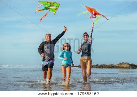 Happy family running at beach with kites. Smiling family flying kite together at seaside.