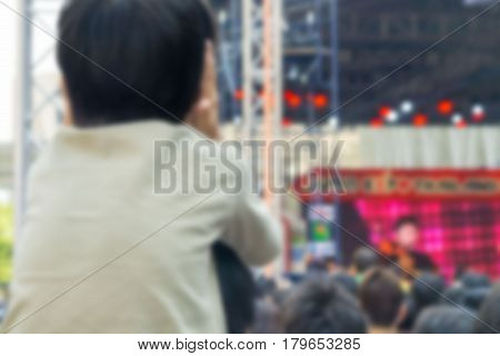 Abstract blurred . A kid cover ear and sitting on the shoulders of his father at outdoor concert