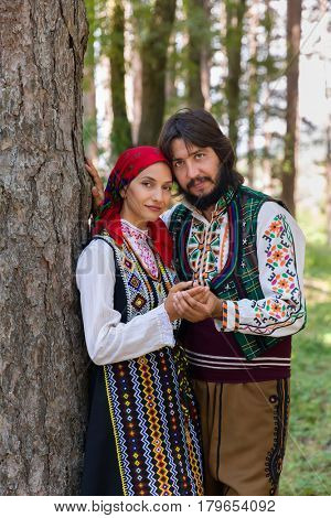 Romantic couple posing in a forest wearing traditional Bulgarian clothing