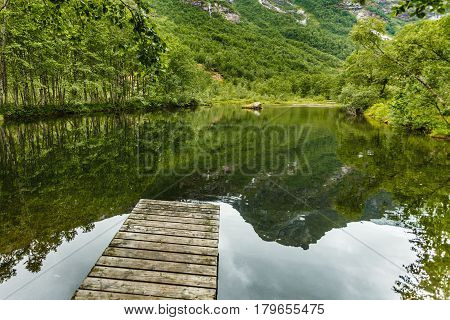 Old Wooden Pier On Lake Pond In Summer