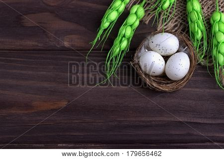 Easter Decoration With Easter Eggs In The Nest Burlap Cloth Green Spikelets.