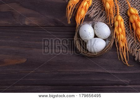 Easter Decoration With Easter Eggs In The Nest Burlap Cloth Orange Spikelets.