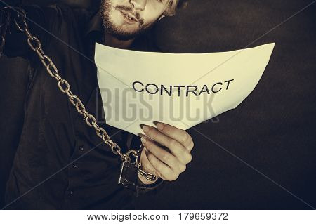Man With Chained Hands Holding Contract