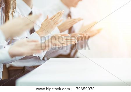 closeup of business team applauding the speaker in the office .the photo has a empty space for your text