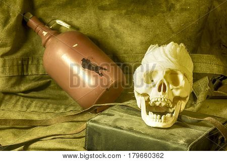 The human skull, lying on a tarpaulin on the background of a bottle with a flare of fear and death