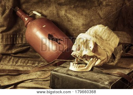 Skull with an open jaw on the background of a bottle lying on a tarpaulin
