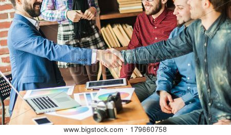 handshake business partners at a meeting in creative office on the background of business team